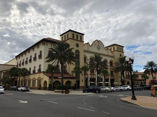 Grosses Gebäude mit der Aufschrift La Reina, Palmen davor.