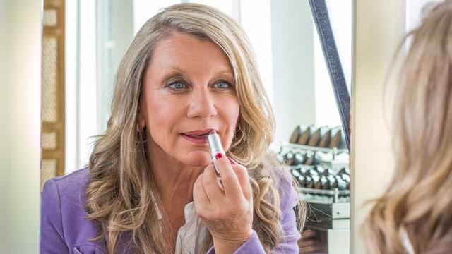 Frau schminkt ihre Lippen im Spiegel.