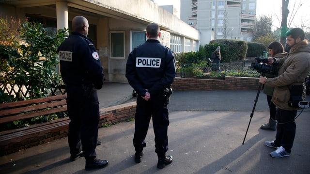 Polizisten und Journalisten vor einem Gebäude.