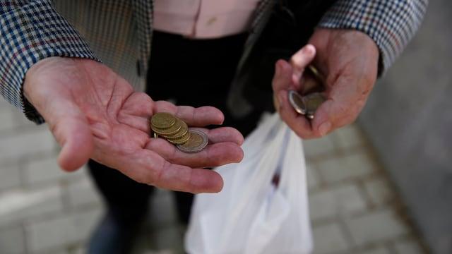 Ein Mann hält einige Münzen in der Hand.