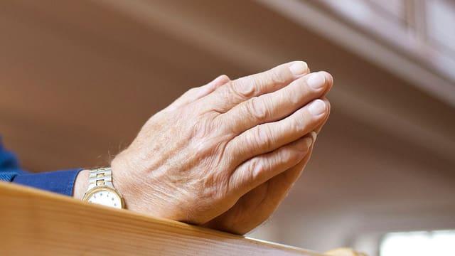 Die gefalteten Hände eines älteren Mannes.