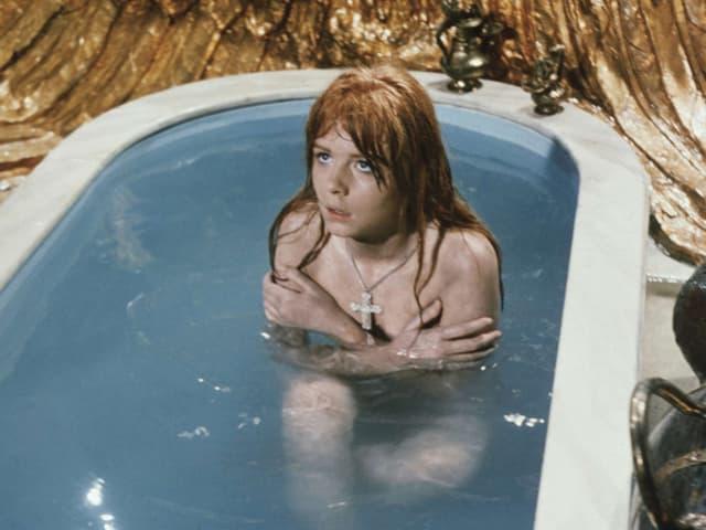 Eine junge Frau sitzt in einer Badewanne und bedeckt ihren Oberkörper.