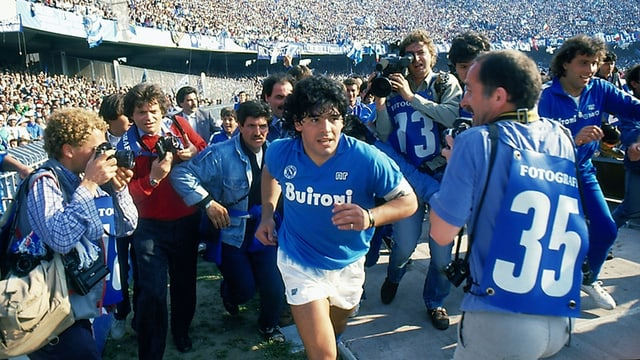 Der Fussballer Diego Maradona läuft umringt von Paparazzi vom Fussballplatz.