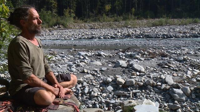 Christoph Trummer meditiert am Fluss.