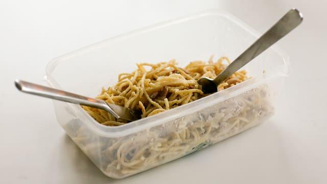 Essen in Plastikgeschirr mit Besteck
