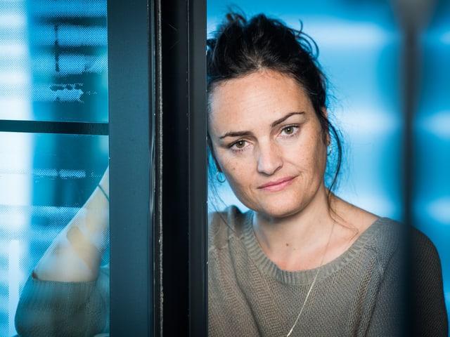 Eine Frau in einem halb geöffneten Fenster.