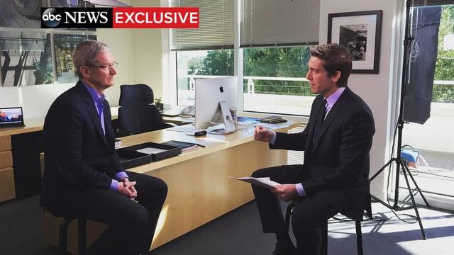 Tim Cook und David Muir auf Barhockern vor einem Schreibtisch mit iMac.