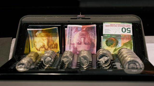 Schweizer Geldnoten und Münzen in einer offenen Kasse.