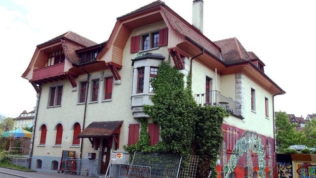 Gelbes Haus mit rotem Dach, Sprayereien an Fassade.