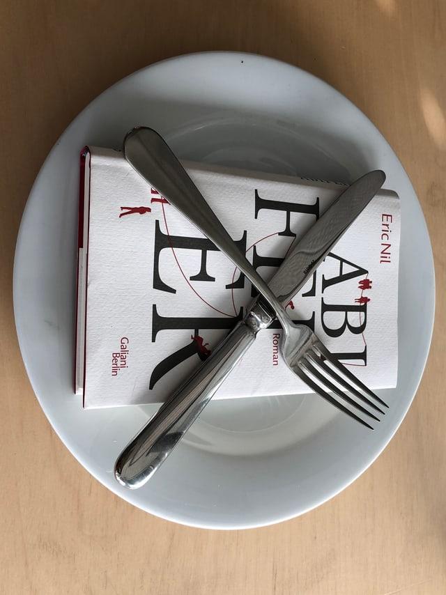 «Abifeier» von Eric Nil liegt auf einem weissen Teller. Messer und Gabel in 20-nach-8-Stellung darüber.
