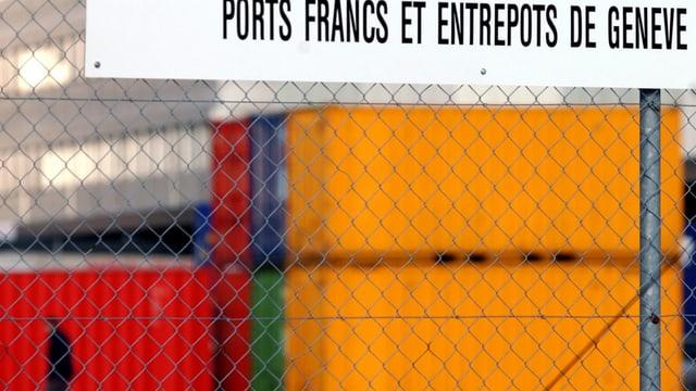 Farbige Container hinter einem Zaun.