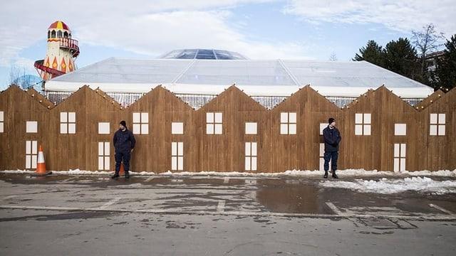 Sicherheitsleute vor einer Holzkulisse, die an eine Reihenhaussiedlung erinnert.