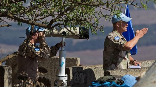 Zwei UNO-Soldaten überwachen mit einem Fernglas die Lage an der Grenze zu Syrien.
