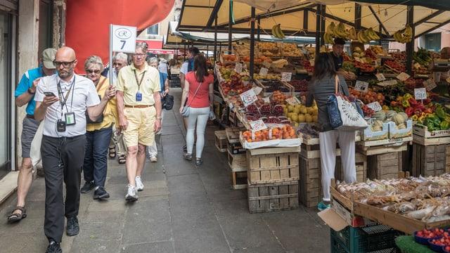 Touristengruppe geht an einem Markt vorbei.