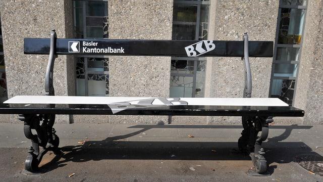 Eine schwarze Sitzbank mit weisser Aufschrift der BKB vor dem Bankgebäude in Riehen.