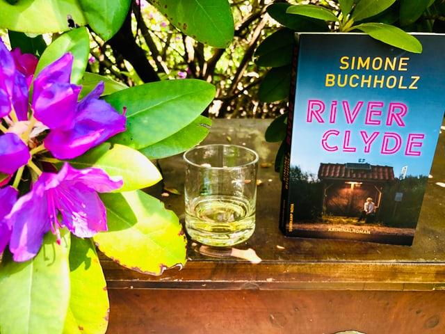 Der Krimi «River Clyde» von Simone Buchholz steht zusammen mit einem Glas Whiskey unter einem Rhododendronbuschunter
