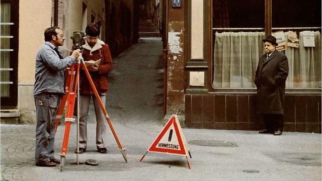 Aufnahme aus den Siebzigerjahren: Zwei Männer vermessen eine Strasse, dahinter Mann mit Hut und Stumpen im Mund