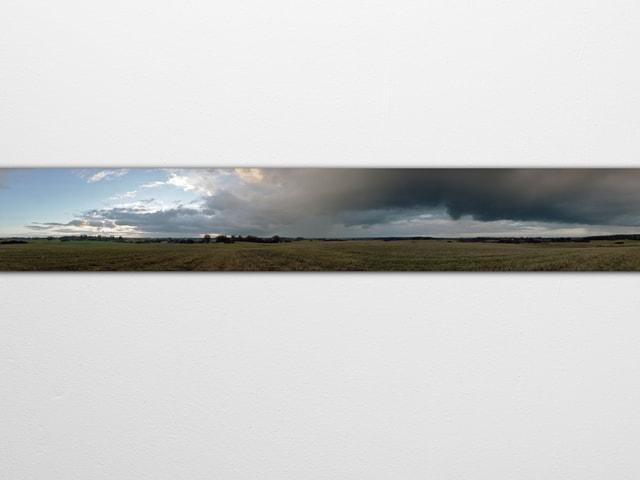 Panoramabild einer Landschaft: Links mit Sonnenschein, rechts Gewitterwolken.