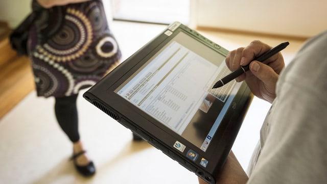 Wohnungsübergabe: Ein Touchpad mit geöffneten Formularen, die Füsse einer Frau