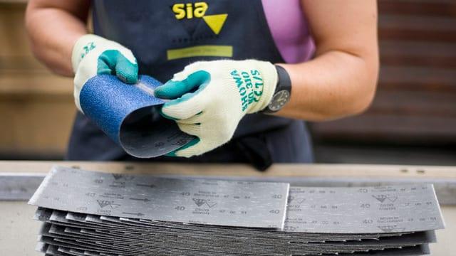 Eine Mitarbeiterin von Sia Abrasives klebt die beiden Enden von Schleifpapierstücken zu Rollen zusammen.