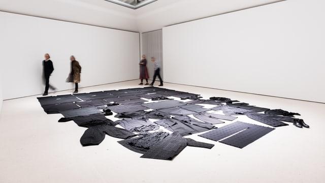Ein Museumsraum: Auf dem Boden sind schwarze Kleider ausgebreitet.
