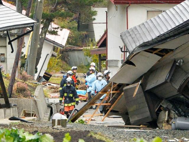 Menschen an eingestürzten Häusern
