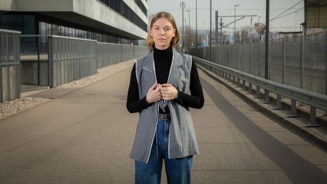 eine junge Frau steht mit einem Anzugs-Muster auf einer Strasse
