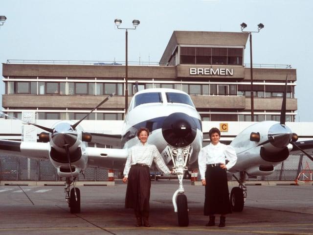 Zwei Frauen in Röcken vor Flugzeug