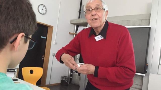 Älterer Mann erklärt einem Buben etwas
