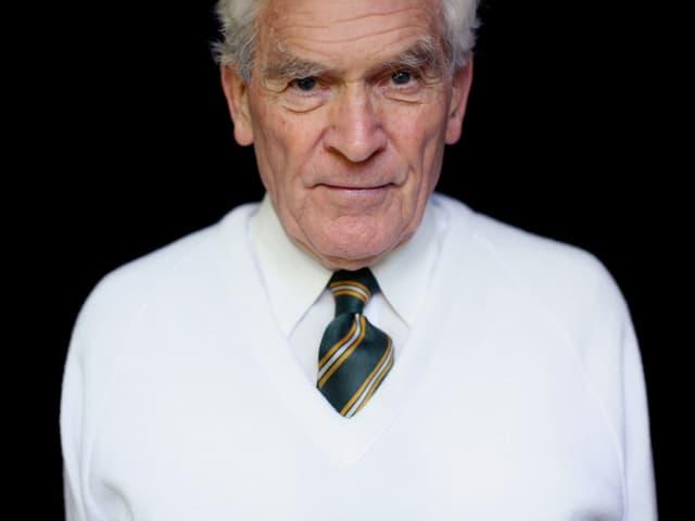 Ein weiss gekleideter älterer Mann vor schwarzem Hintergrund.