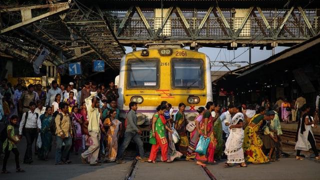 Menschen gehen vor einem Zug durch.
