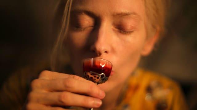 Tilda-Swinton als Vampir trinkt Blut aus einem kunstvollen Gefäss, ähnlich wie jemand, der Wein trinkt.