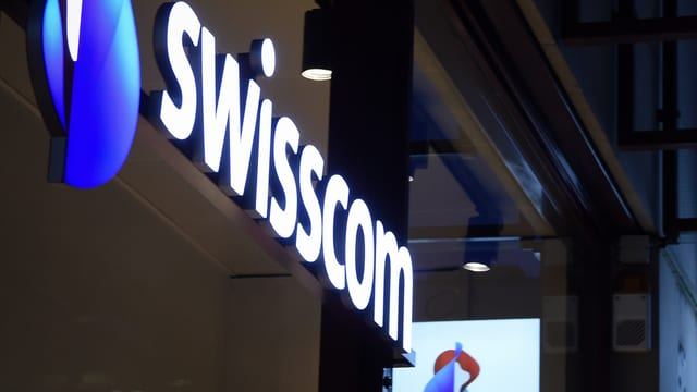 Logo da Swisscom illuminà vi d'ina chasa.