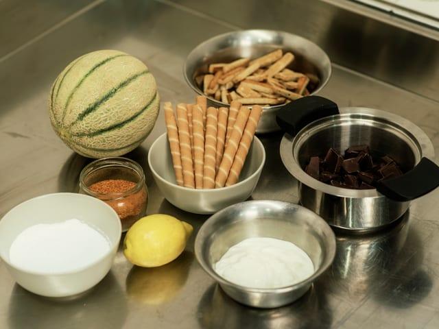 Das sind die Zutaten für unser Kultglacé: Joghurt, Zitrone, eine Prise Chili, Puderzucker, geschmolzene Schoggi, Hüppen oder Nussstägeli und Melone.