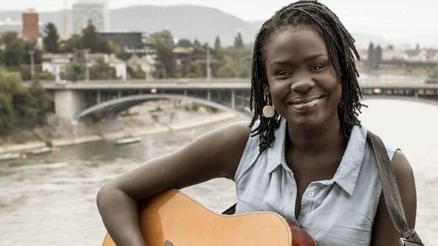 Eine junge Frau sitzt auf der Basel Pfalz mit einer Gitarre in der Hand. Sie strahlt.