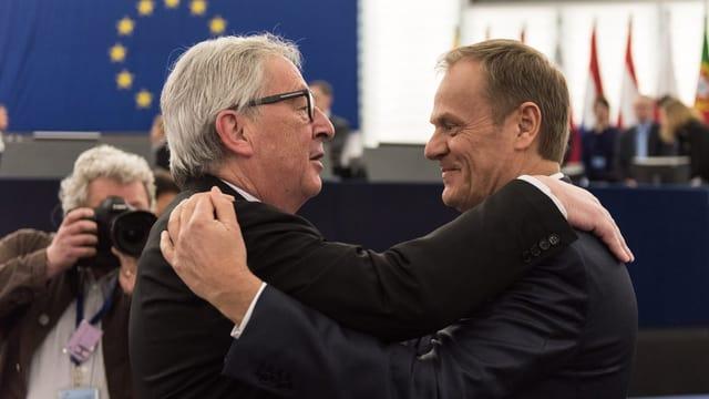 EU-Ratspräsident Tusk und EU-Kommissionspräsident Juncker halten sich in den Armen.