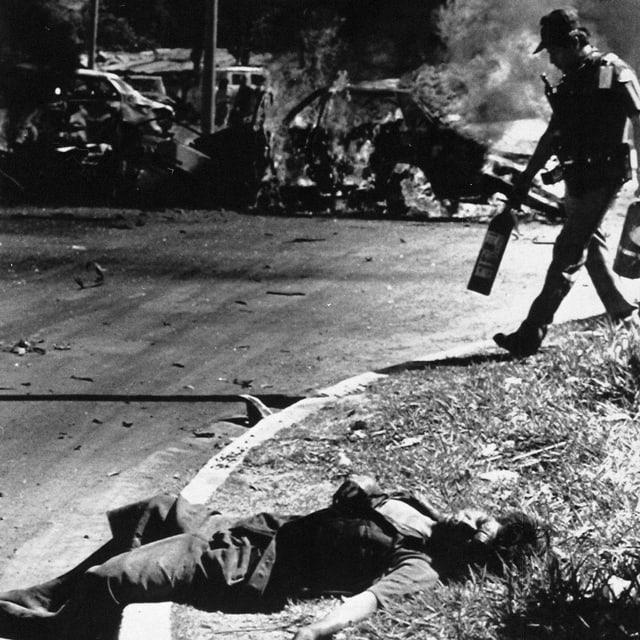Ein verletzter Soldat liegt auf einer Strasse.