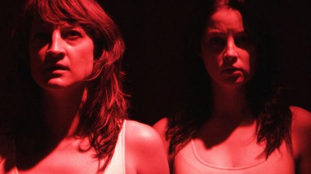 Filmstill aus «Raze», zwei rotbeleuchtete Frauenoberkörper.