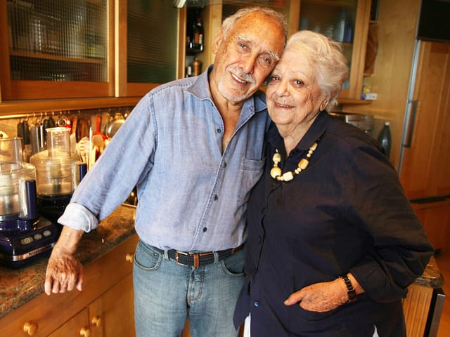 Ein älteres Paar steht in einer Küche – Er hält den Arm um sie.
