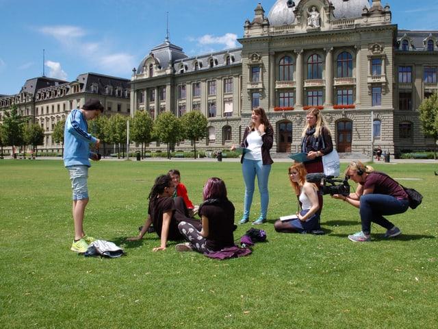 Die Teilnehmer des Camps führen vor dem Gebäude der Universität Bern eine Umfrage bei Passanten durch.