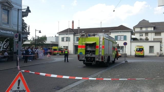 Feuerwehrauto hinter einer Abschrankung vor dem Bahnhofsgebäude.