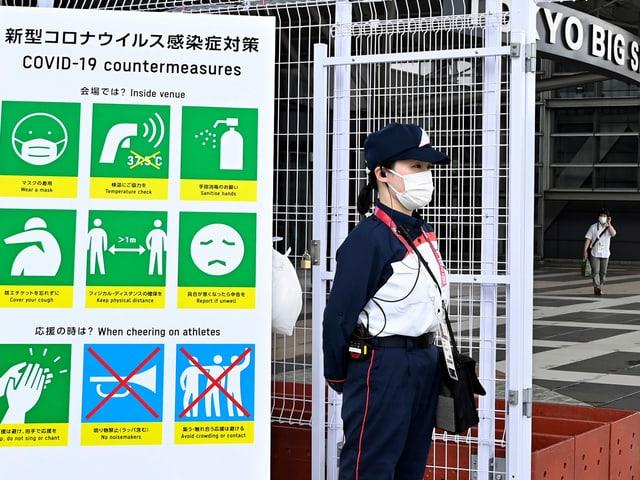 Frau vor Plakat mit Corona-Schutzmassnahmen in Tokio