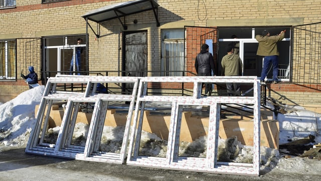 Männer setzen neue Fenster ein.