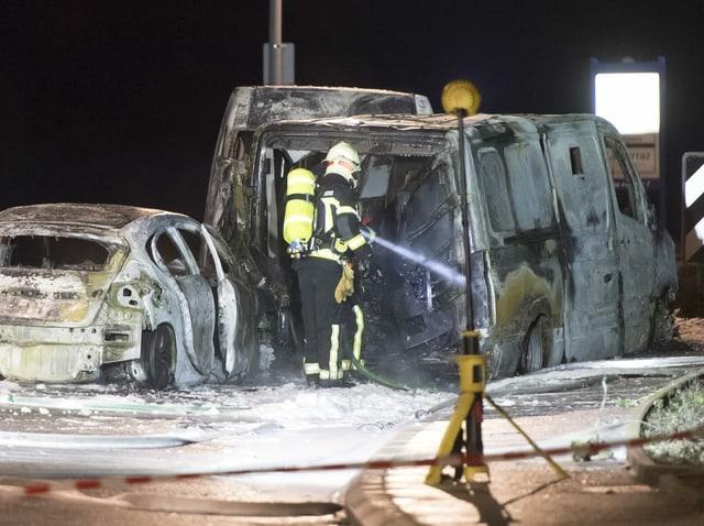 Ein Feuerwehrmann löscht einen ausgebrannten Geldtransporter