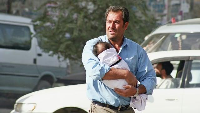 Ein Mann mit einem Kind in den Armen geht über eine Strasse.