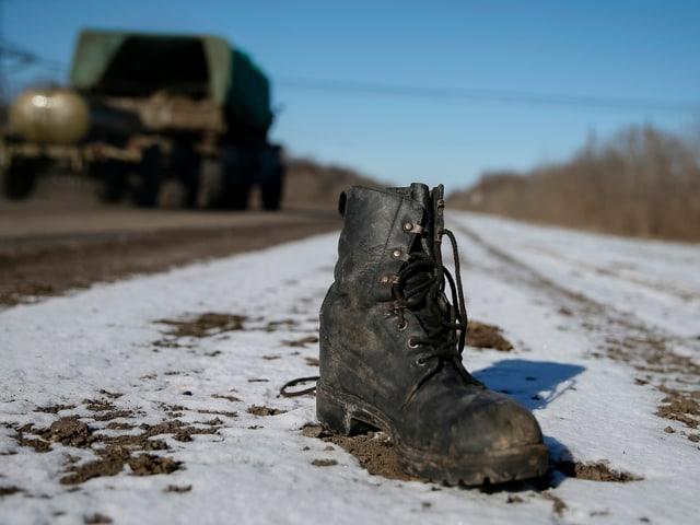 ein Armeeschuh liegt auf der Strasse in der Ostukraine