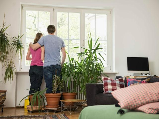 Mann und Frau stehen in ihrer Wohnung.