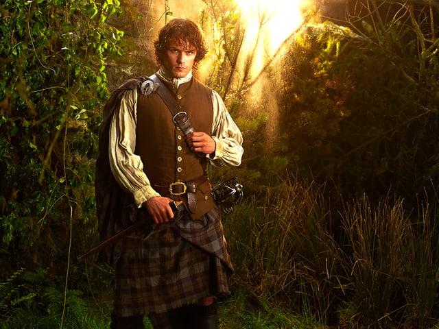 Ein Mann mit Schottenrock im Wald.