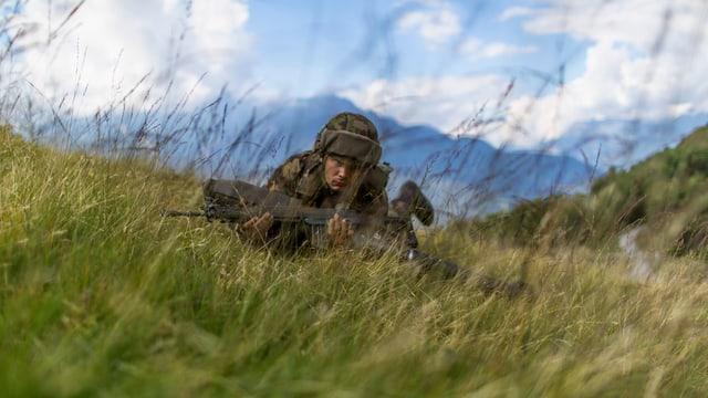 Ein Soldat robbt auf einer Alp im hohen Gras, Aufnahme frontal von vorn.
