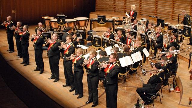 Eine Grossformation mit Bläsern auf einer Konzertbühne.